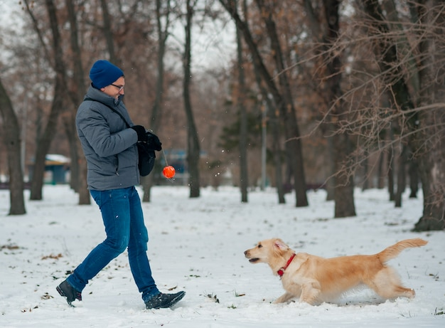 Golden retriever playing with his owner walking outdoors winter day, warm clothing. love and care for the pet.