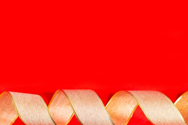 Золотая лента на красном фоне. завитки золотой упаковочной ленты на красном фоне