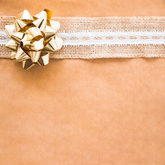 Golden ribbon bow and striped on brown paper