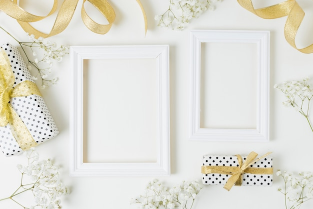 Golden ribbon; gift boxes; baby's-breath flowers near the wooden frame on white backdrop