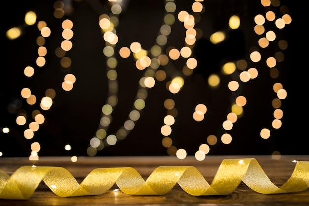 Golden ribbon lying near blurred lights