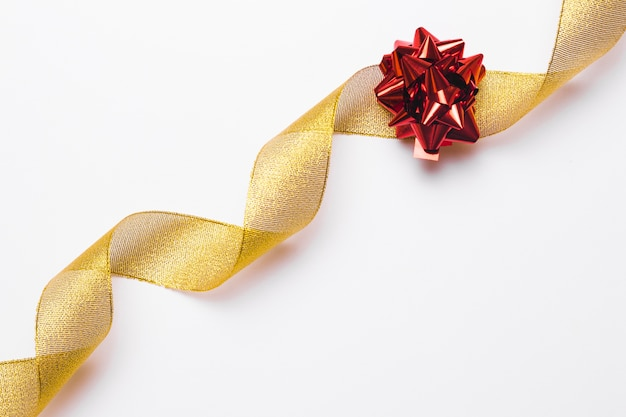 Golden ribbon and red bow in background