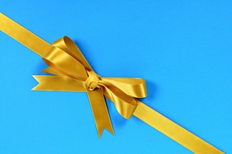 Golden ribbon with blue gift