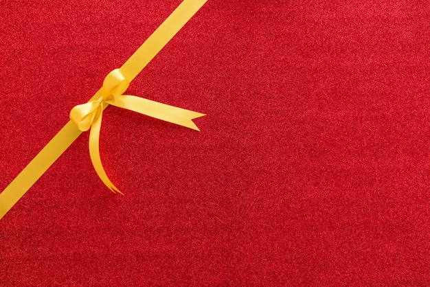 Golden ribbon with bow on red glitter paper background, top view border design