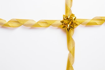 Golden ribbons and bow on cross