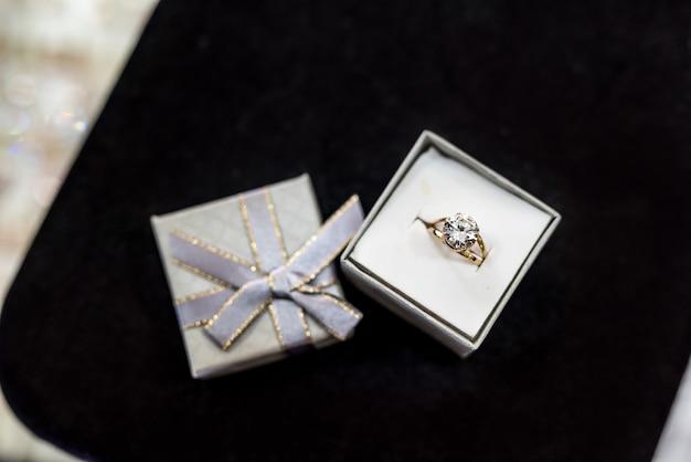 銀のギフトボックスに大きな石と金の指輪
