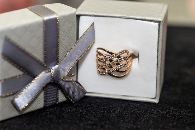 Золотое кольцо с бриллиантом в коробке, изолированной на черном