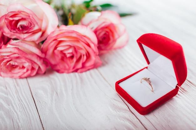 Золотое кольцо с драгоценными камнями в красной подарочной коробке и букет роз