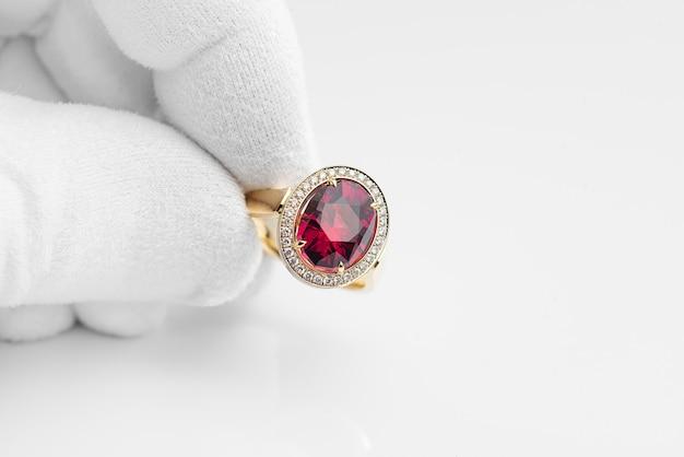 흰색 장갑에 보석상 손에 로돌라이트 보석과 다이아몬드가 있는 황금 반지