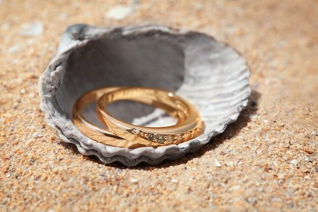 砂の上の貝殻の金の指輪、クローズアップ。ビーチの結婚式のコンセプト