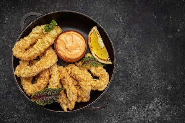 Золотые кольца кальмаров фри на круглой сковороде с соусом из зелени и лимона на темном фоне