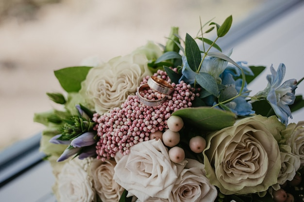 Golden rings on wedding bouquet with beautiful roses