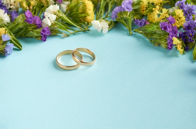 Golden rings with colored flowers on blue surface, wedding template.