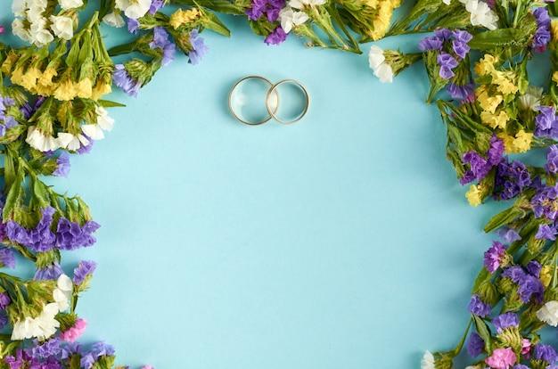 결혼식 서식 파일 파란색 표면에 착 색된 한 꽃과 황금 반지.