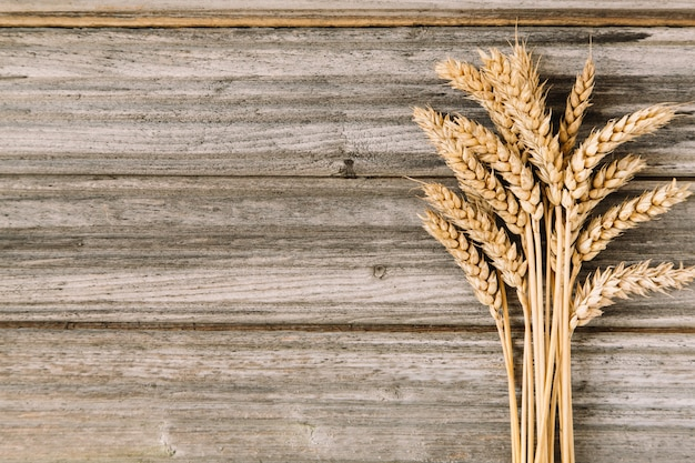 Golden ripe wheat on old wooden background