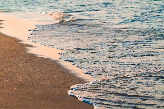 바다 해변의 황금빛 모래와 파도
