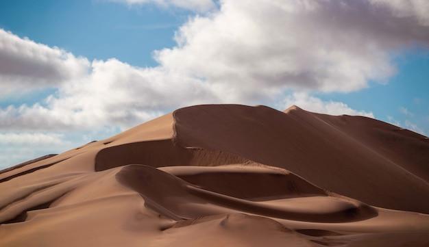 Золотая песчаная дюна 7 и белые облака в солнечный день