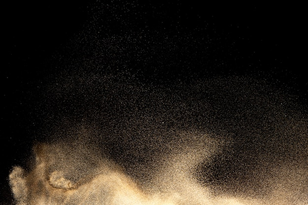 Golden sand explosion on black background