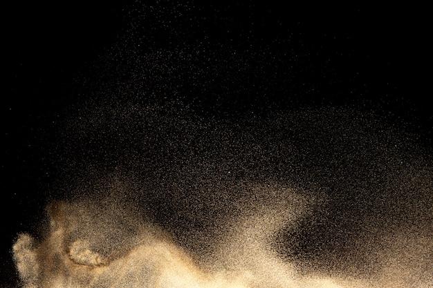 Golden sand explosion on black background