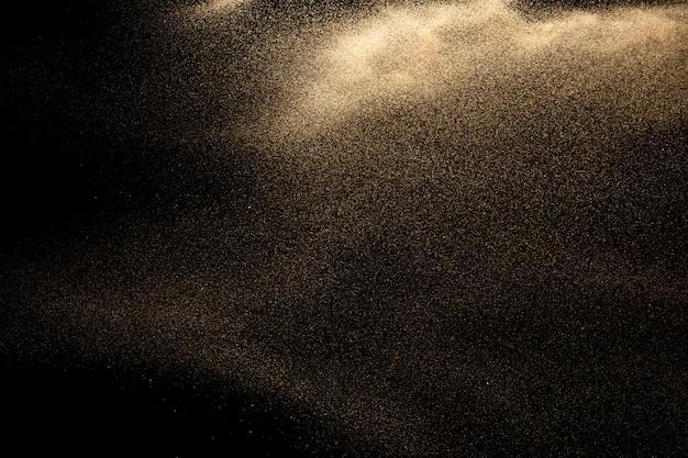 黒の背景に黄金の砂の爆発