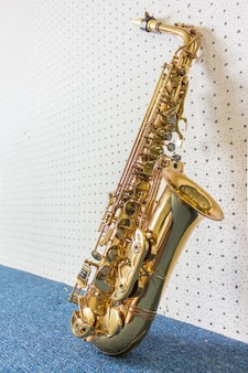 Golden saxophone on white and blue wall background