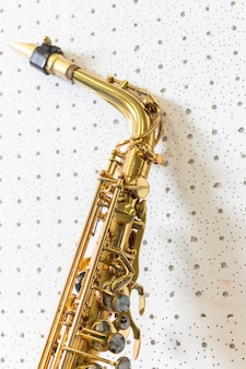 Golden saxophone on white wall background