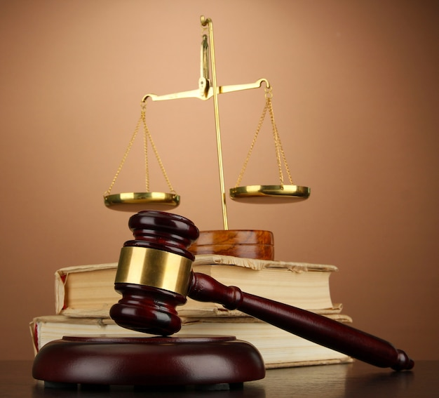 Golden scales of justice, gavel and books on brown