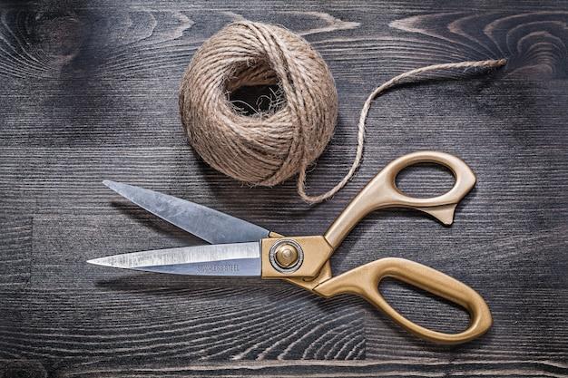 Golden scissors hank of rope on vintage wooden board