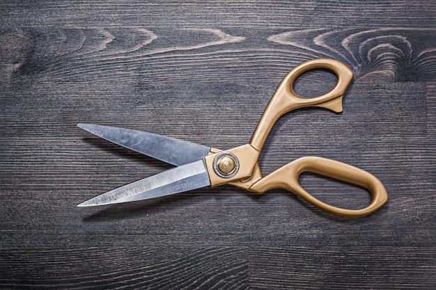 Golden scissors on vintage wooden board top view