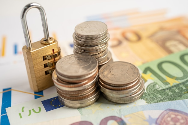 Golden security digital password lock key and coins with with euro banknotes