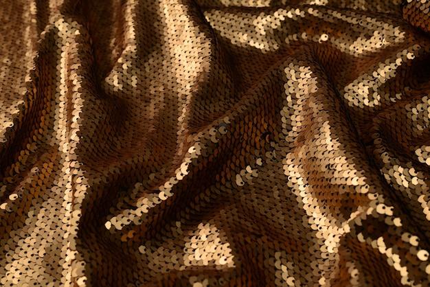 Golden sequins fabric texture. top view.