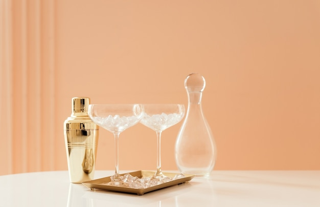 Golden shaker, elegant glasses with cocktail, decanter and ice cubes. party set, bar concept with copy space.