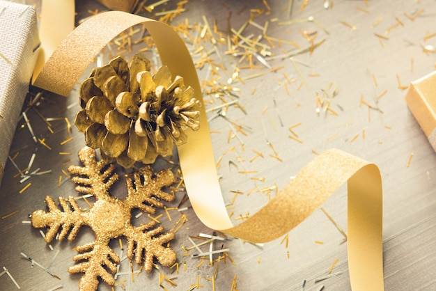 Golden shimmer christmas decorating items on wood background