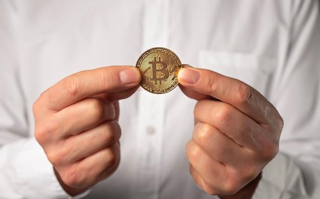 男性の手で金色に輝くビットコインコインをクローズアップ。
