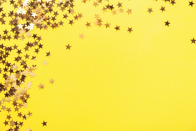 Golden shining stars confetti on yellow