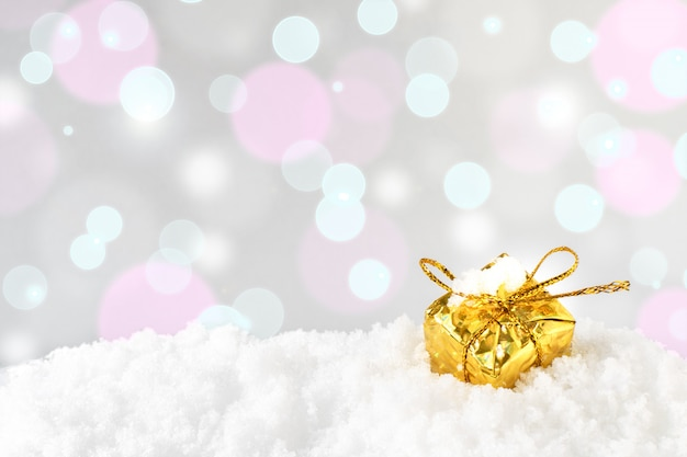 A golden shiny decorative christmas or new year gift box with a bow is standing in the snow against the background