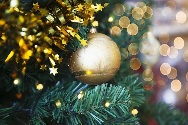 ぼやけた光とクリスマスツリーの黄金の光沢のあるきらびやかなボール。休日のコンセプト。閉じる。