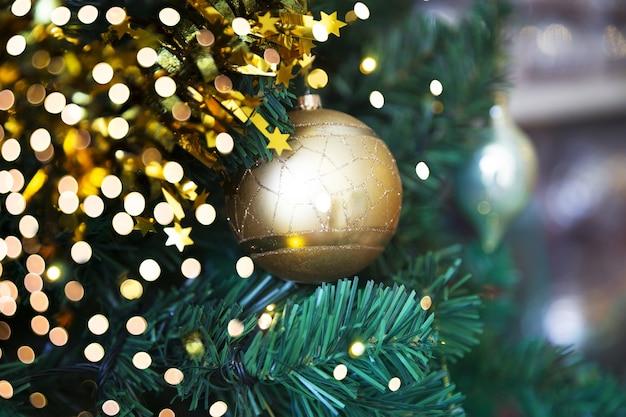 ぼやけた星の花輪とクリスマスツリーの黄金の光沢のあるきらびやかなボール