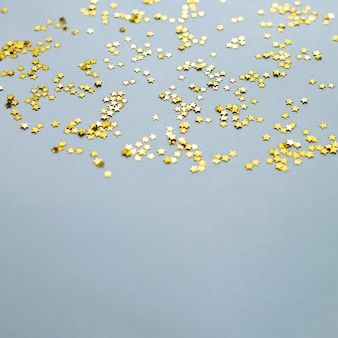 Golden shiny stars glitter or confetti on gray background with copy space