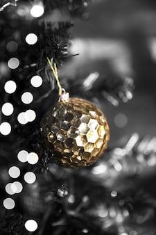 ぼやけた光とクリスマスツリーの黄金の光沢のあるテクスチャボール。休日のコンセプト。閉じる。