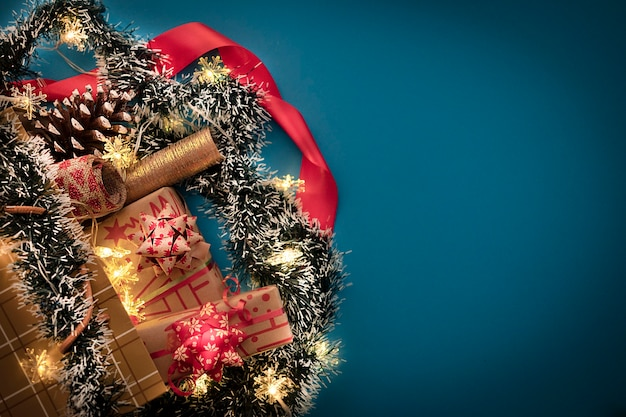 A golden shopping bag with christmas presents and ornaments on a blue background illuminated by yellow lights. copy space