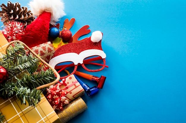 파란색 배경에 크리스마스 선물, 산타 모자, 장식품이 있는 황금 쇼핑백. 복사 공간