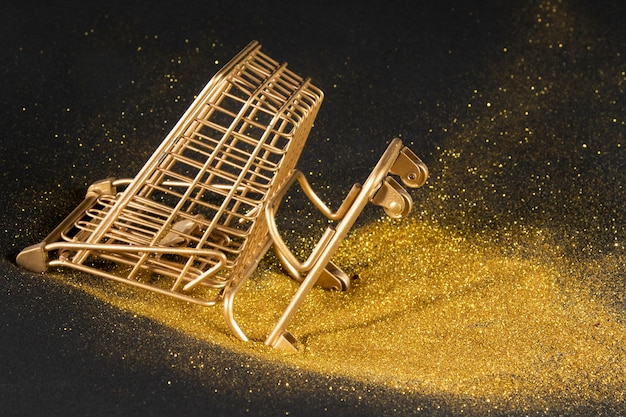 Golden shopping cart on black background