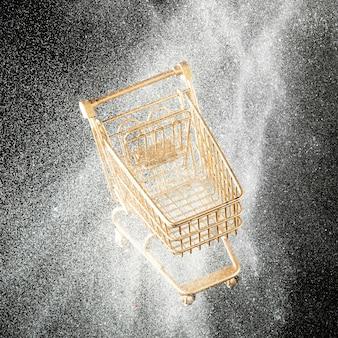 Golden shopping cart in white glitter close-up