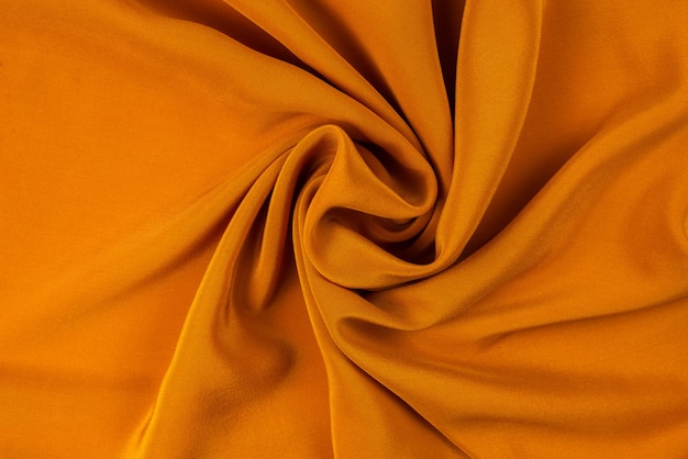 Golden silk or satin luxury fabric texture can use as abstract background. top view.