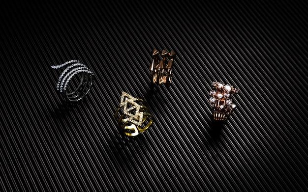 黒のテクスチャ紙の上の金、銀、銅のリングコレクション