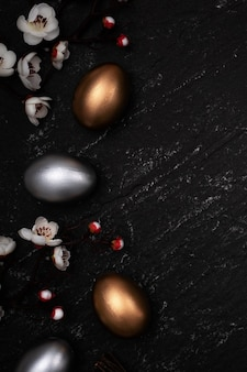 Golden and silver easter eggs with plum blossom flower on slate table background.