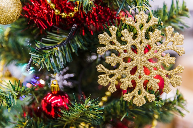 Golden snowflake on green branches of christmas tree. new year decorations