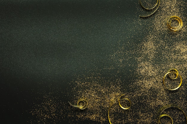 Golden sparkles and ribbons on black background. festive .