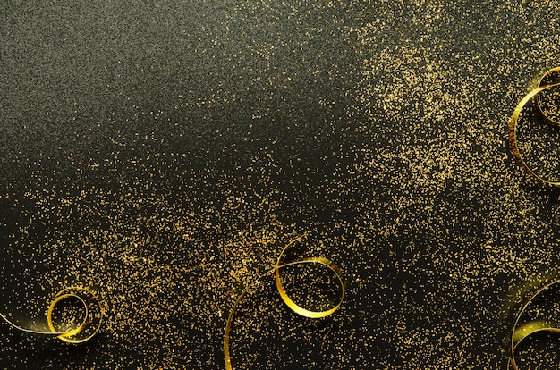 Golden sparkles and ribbons on black